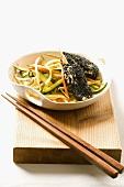 Chicken kebab with black sesame seeds on a bed of vegetables