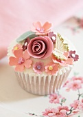 A Louise cupcake decorated with sugar flowers and butterflies