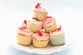 A stack of cupcakes topped with pink frosting on a plate