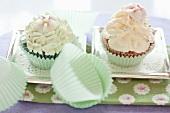 Two cupcakes topped with frosting on silver trays
