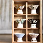 Assorted Sake Glasses on a Wooden Shelf