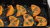 Spiced pumpkin wedges on a baking tray
