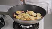 Bratkartoffeln mit Speckwürfeln in einer Pfanne schwenken