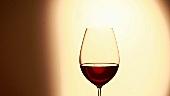 Ein Tropfen fällt in ein Glas Rotwein
