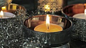 A burning tealight with Christmas decorations