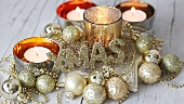 Christmas decorations with tealights and golden baubles