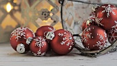 Christmas baubles and burning candles in the backgrounds