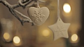 A heart-shaped decoration and a star-shaped decoration hanging on a branch