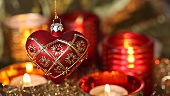 A heart-shaped Christmas tree decoration and tealights