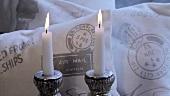Zwei Kerzen vor Dekokissen