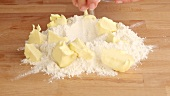 Chopped butter on a pile of flour being sprinkled with salt