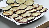 Fried aubergine slices being dried on kitchen paper