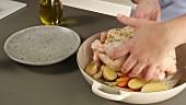 Gemüse mit Öl beträufeln, würzen und das Hähnchen darauf legen