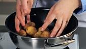 Ungeschälte Kartoffeln in einen Topf geben