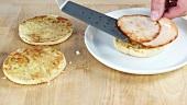 English Muffins mit gebratenen Schinkenscheiben belegen