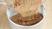 Teig für Karottenkuchen in eine vorbereitete Backform füllen