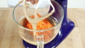 Carrot cake being made: grated carrot being added to cake mixture