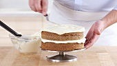 A carrot cake being spread with cream cheese creme