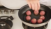 Meat balls being placed in a pan and fried