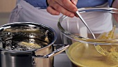 Vegetables in chickpea batter being transferred to a pot of hot oil