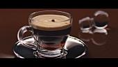 Tropfen fallen in eine Tasse Espresso