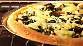 A spinach, sheep's cheese and olive pizza in an oven