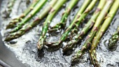 Green asparagus being fried in a pan of butter