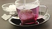Hot water being poured over a fruit tea bag in a cup