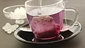 Früchtetee im Beutel mit heißem Wasser übergiessen
