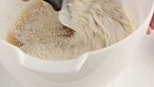 Flour being added to banana bread dough