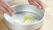 A deep baking tin being brushed with olive oil