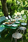 Set table and motley collection of chairs beneath tree for idyllic meal in garden