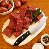 Cubed Grass Fed Beef Sirloin Tips on Cutting Board; Peppercorns, Salt and Red Potatoes