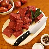 Rindfleischwürfel auf Schneidebrett, Pfeffer, Salz, Rote Kartoffeln