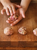 A child's hands shaping meatballs
