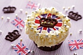 A cupcake topped with cream and a Union Jack surrounded by chocolate crowns