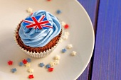 A chocolate cupcake topped with blue buttercream and a Union Jack