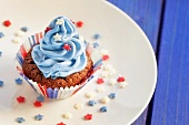A chocolate cupcake top with blue cream