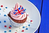 A chocolate cupcake topped with pink cream and a Union Jack