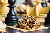 Nut brittle drizzled with chocolate on a chessboard