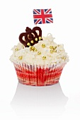 A cupcake decorated with golden beans, a chocolate crown and a Union Jack