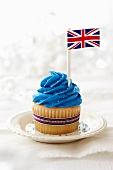 A vanilla cupcake topped with blue frosting and a British flag