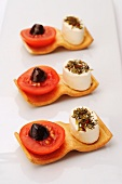 Canapes with cream cheese, tomatoes and olives