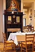 Restauranttische vor offenem Kamin mit antiker Holzeinfassung und modernem Gemälde darüber