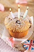 A cupcake with three candles with Union Jack decorations and rose petals next to it
