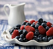 Fresh Blueberries and Raspberries on a White Dish; Pitcher