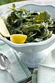 Steamed Greens (Horta) in a Bowl with Lemon Wedges