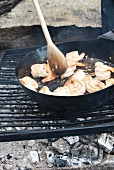 Cooking Shrimp in a Cast Iron Pan Over an Outdoor Fire