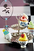 Cupcakes decorated with colourful butter cream in tea cups