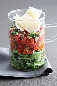 Layered salad made with rocket, tuna tartar, capers and Parmesan